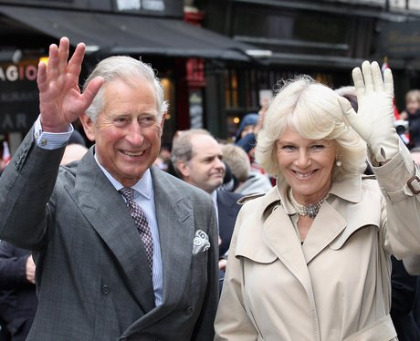 The Prince of Wales and Duchess of Cornwall smile and wave