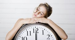 blonde Woman resting on giant alarm clock