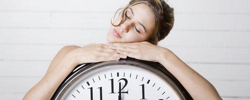 blonde Woman resting on giant alarm clock