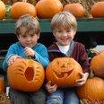 two children pumpkin carving