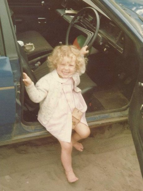 Little Rachael by a car on the beach
