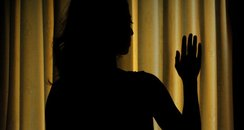 Silhouette of female model by curtains