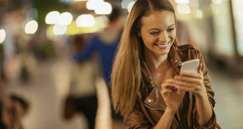 Woman using mobile phone and smiling