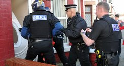 Police  break down door in drugs raids